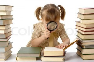 Little girl looking at book through magnifier